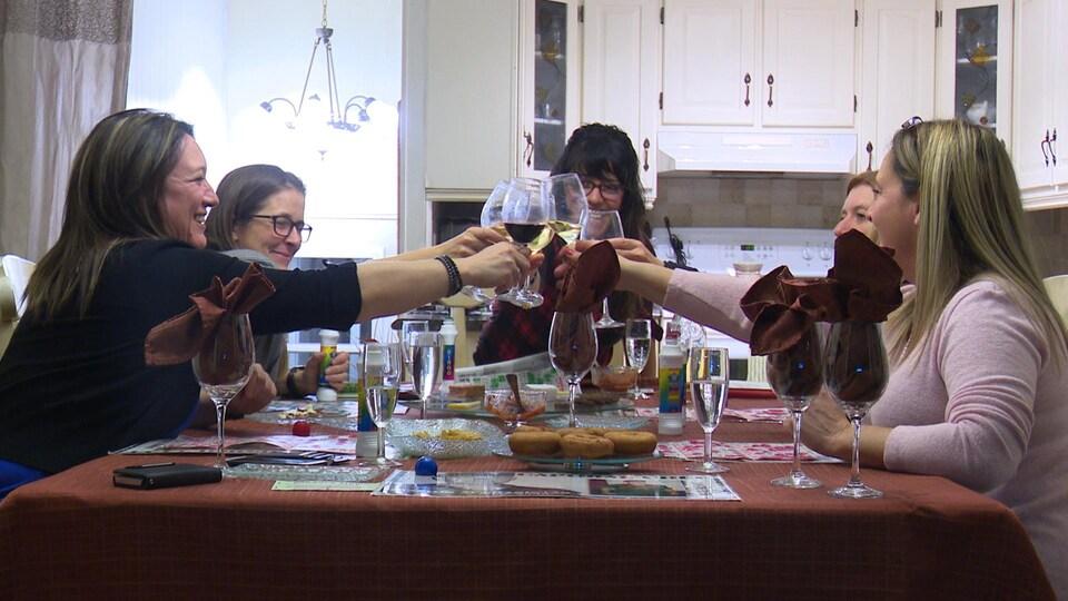 Cinq femmes font un «chin-chin» avec leurs coupes de vin, des cartes de bingo devant elles.