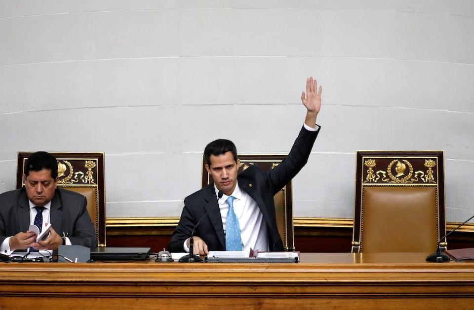 Un homme assis derrière un bureau, lève sa main gauche. Un autre homme est assis à côté de lui.
