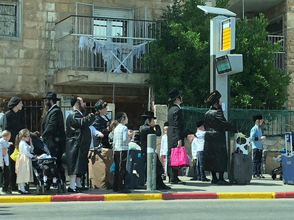 Longue file composée d'hommes, de femmes et d'enfants avec leurs valises.