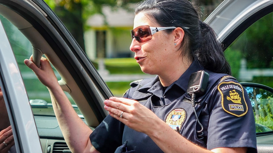 La sergente Julie Marcotte du SPVQ discute avec une collègue à l'extérieur d'une voiture de patrouille