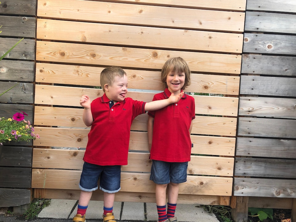 Deux jumeaux de cinq ans vêtus d'un polo rouge sont accotés sur une palissade de bois.