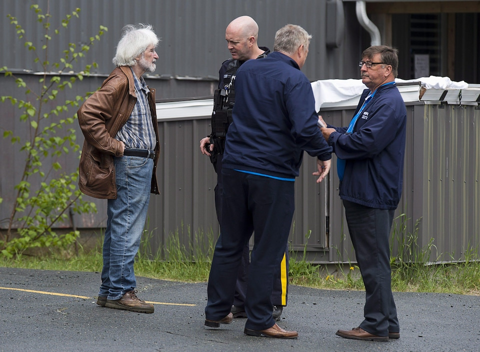 Felix Cacchione, left, director Nova Scotia's Serious Incident Response Team, along with two of his staff, right, talks with an RCMP officer at a shooting which left one person dead in Dartmouth, N.S., on Saturday, May 26, 2018. SIRT investigates all serious incidents involving police. THE CANADIAN PRESS/Andrew Vaughan
