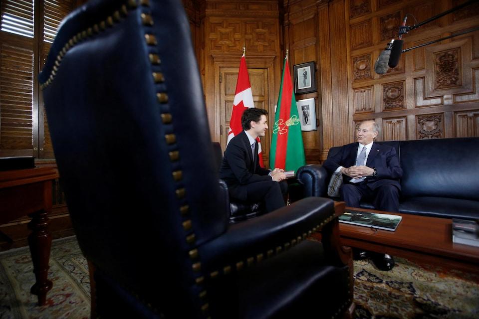 Les deux hommes sont assis de biais sur de magnifiques divans dans un bâtiment du parlement canadien,
