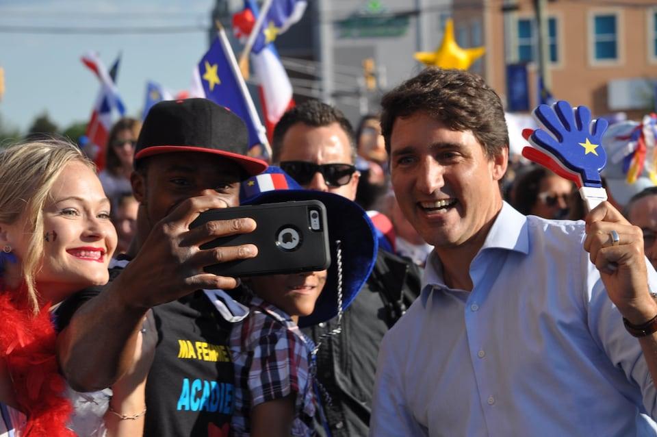 Un homme avec un t-shirt « Ma femme est acadienne » prend un selfie avec Justin Trudeau dans le Tintamarre, le 15 août 2019 à Dieppe.