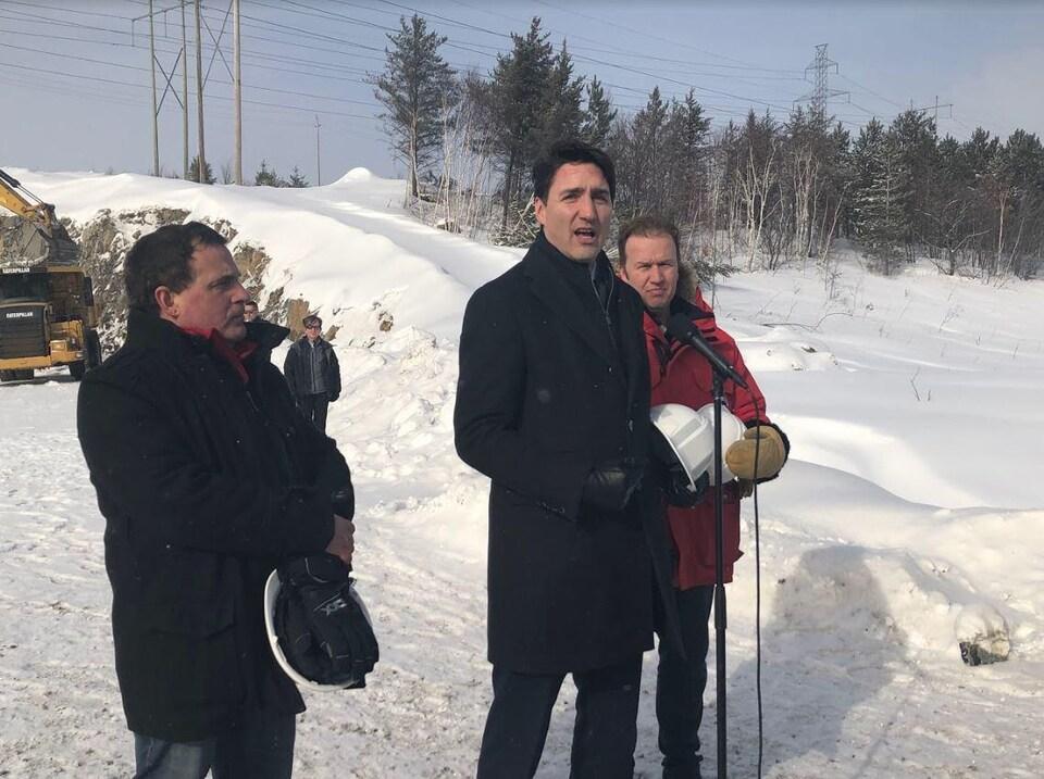 Trois hommes à l'extérieur dans un paysage hivernal.