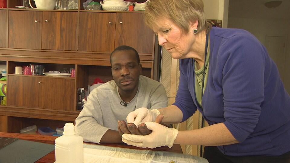 Une infirmière tient la main d'homme et y applique des soins.