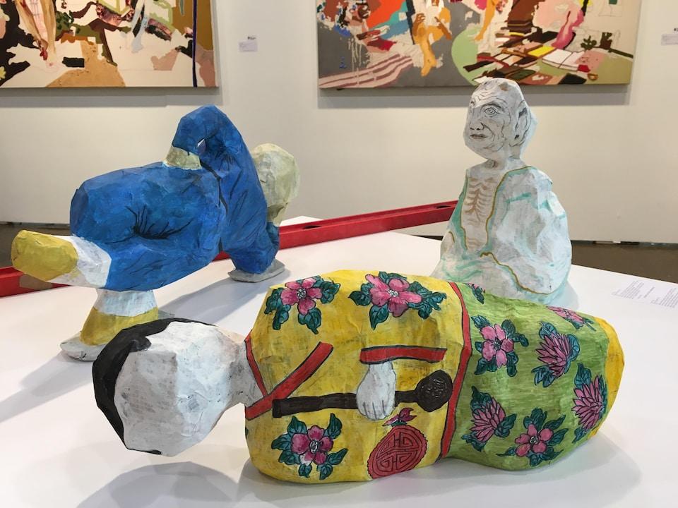 Deux statues représentent des personnes couchées sur le sol de différentes couleurs. Une statue représente une personne assise sur les genoux.