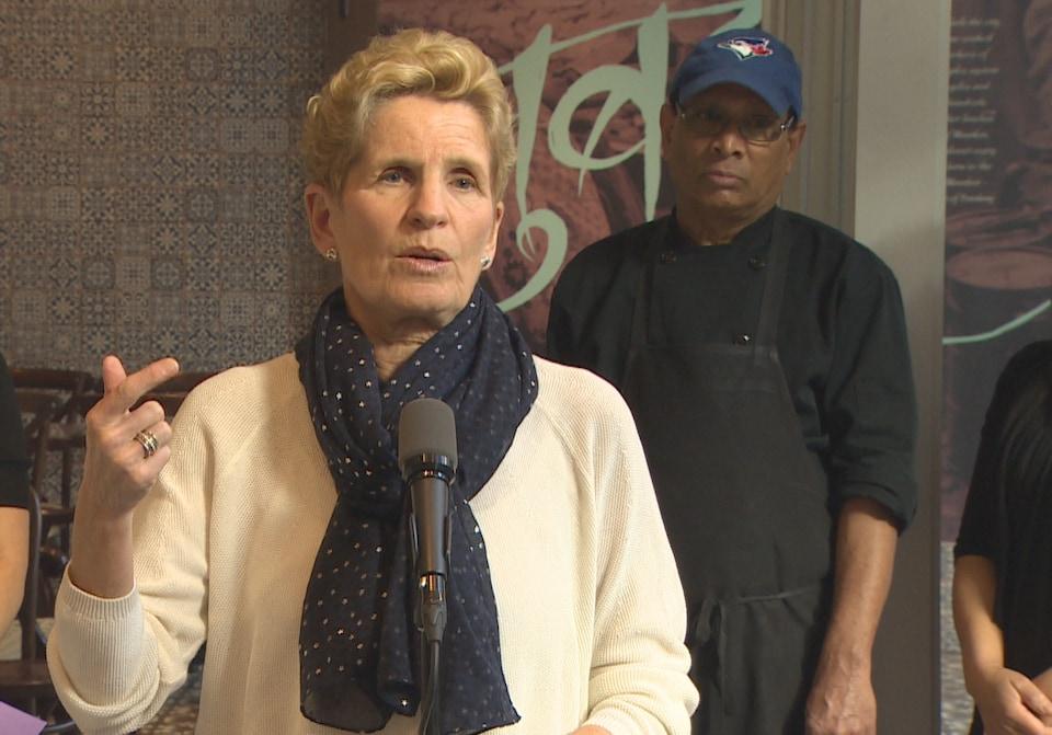 Kathleen Wynne qui parle debout devant un micro.