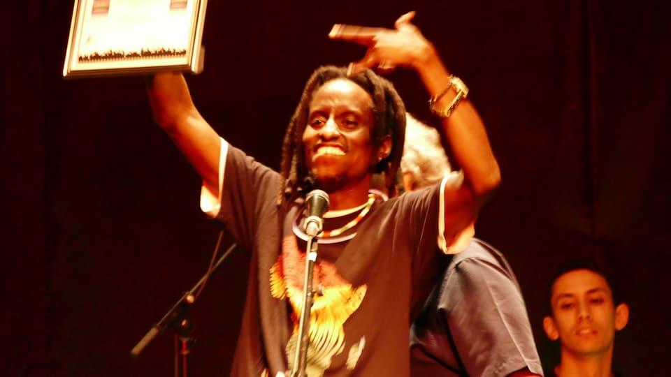 Kaya free sur scène exultant de bonheur en présentant son premier prix, dans un cadre doré.