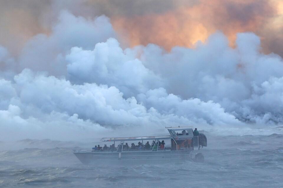 Un bateau s'approche de l'endroit où la lave entre en contact avec l'eau.