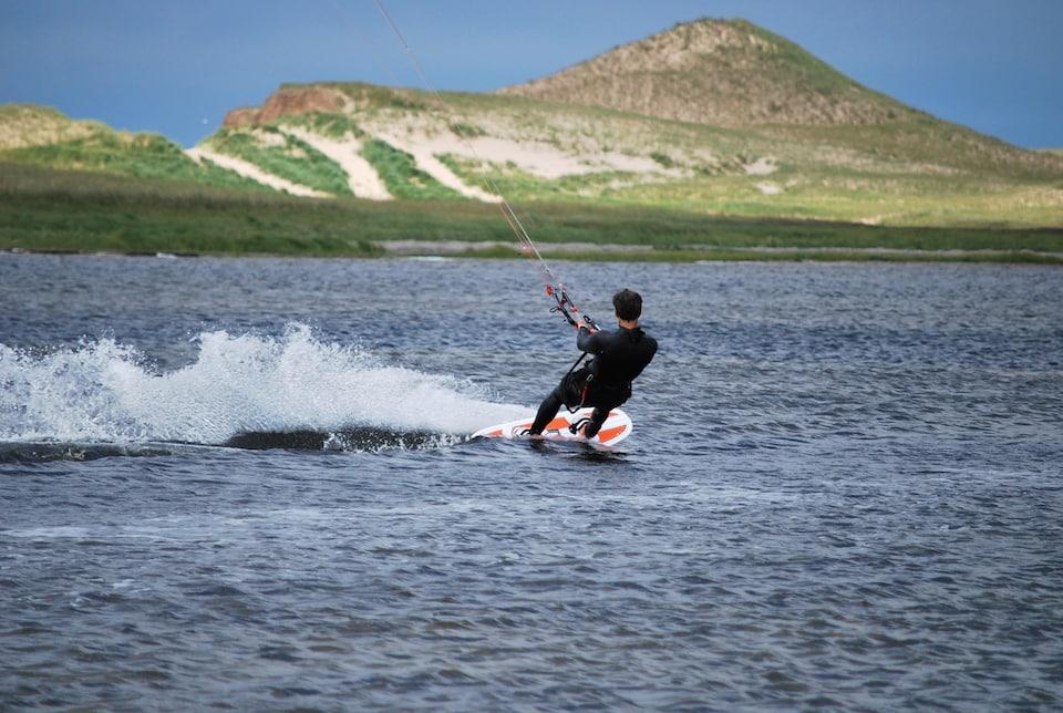 Un homme fait du kitesurf sur l'eau avec une montagne verdoyante à l'arrière.