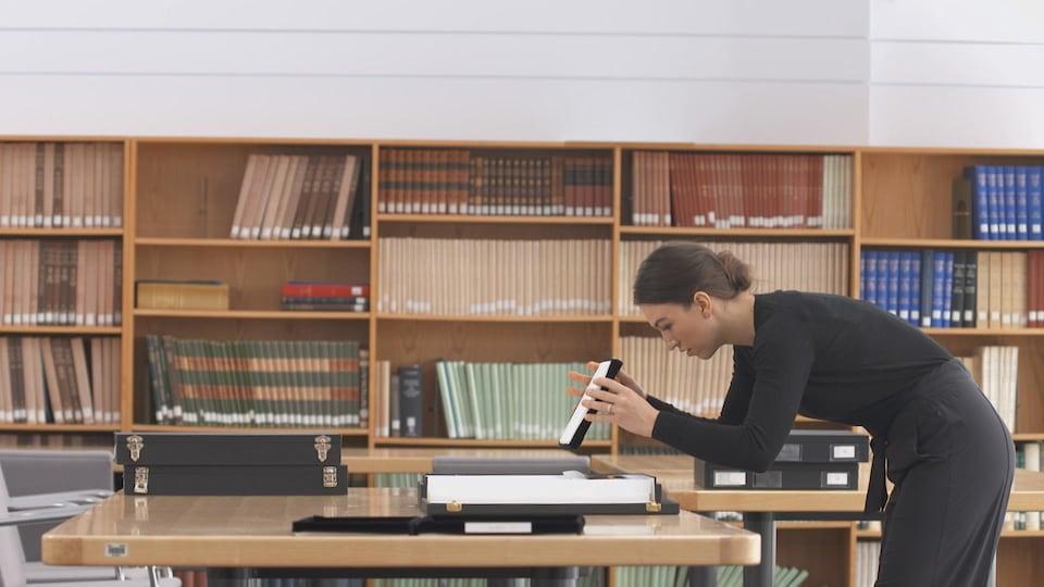 On voit Mme Kozachuk, penchée, de profil, qui examine des daguerréotypes posés sur une table. Derrière elle, on voit des livres sur les étagères d'une bibliothèque.