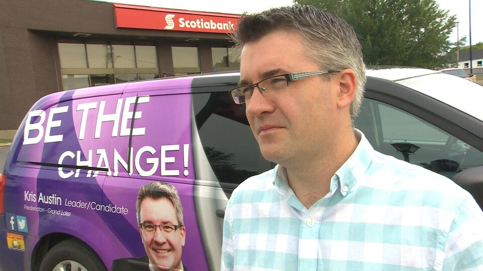 Kris Austin se tient debout devant son véhicule de campagne.
