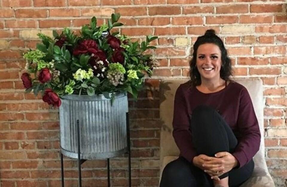 Kyra Klassen souriante est assise près d'un pot de fleurs.