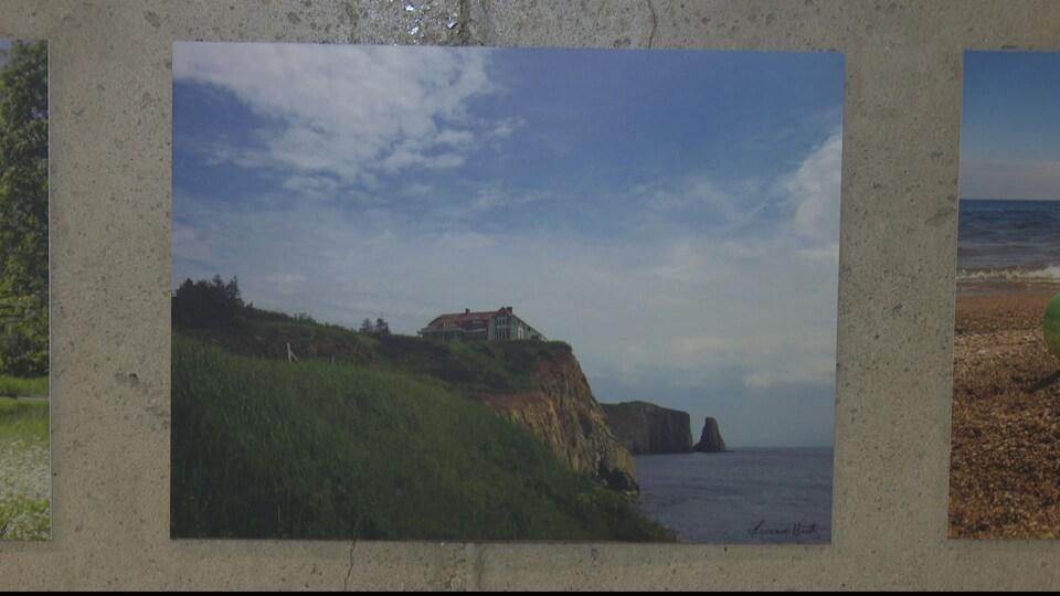 Photographie d'une maison sur une montage près d'une colline bercé par la mer. La signature de l'artiste apparaît au bas, il s'agit de Francine Huet.