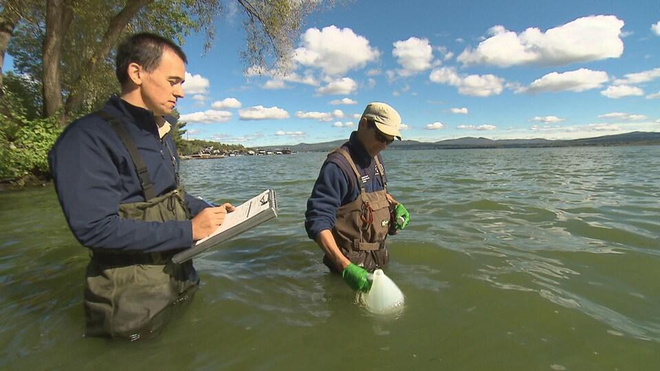 On voit deux hommes debout dans le lac, l'eau jusqu'aux hanches. Ils sont munis de combinaisons. L'un d'eux prend un échantillon d'eau à l'aide d'une bouteille de plastique. L'autre écrit sur un calepin.
