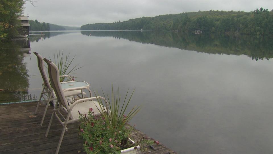 Des chaises sur un quai sur le bord du lac.
