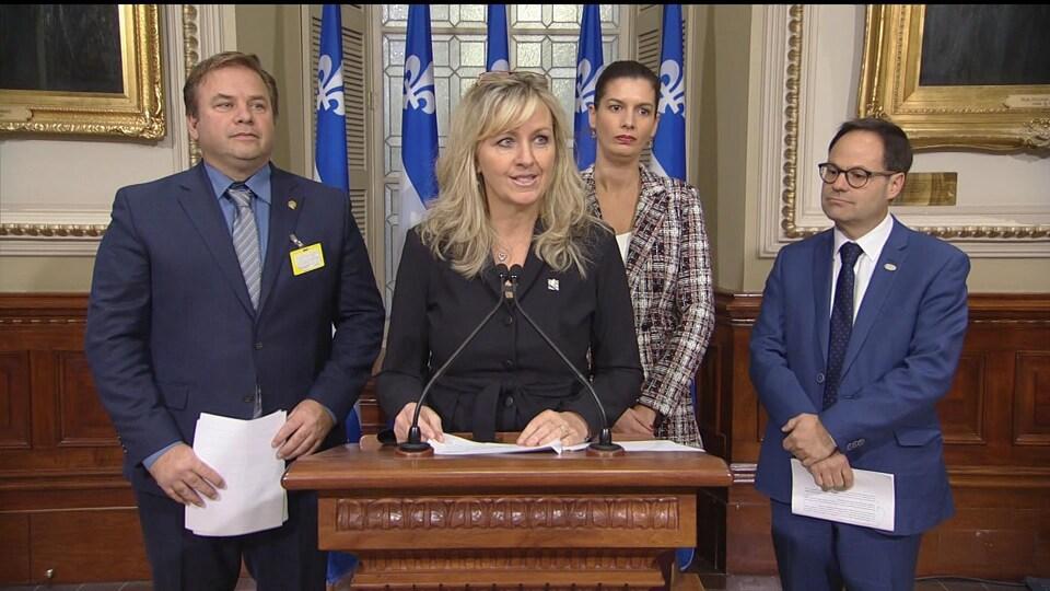 Mme Laforest, au podium, est entourée de deux hommes. La ministre Guilbault se trouve derrière elle.
