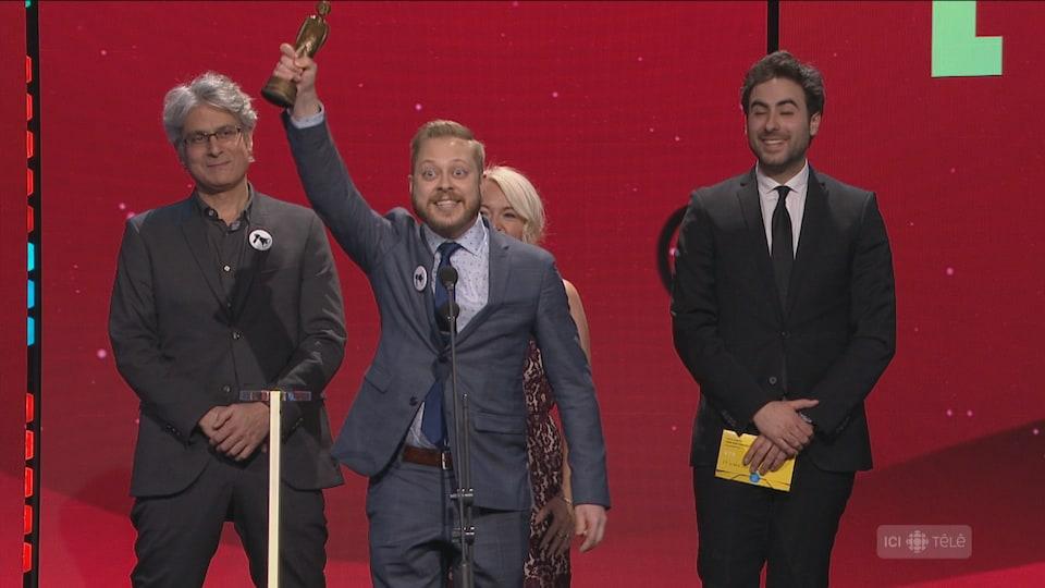 Un homme brandit un trophée sur scène, victorieux.