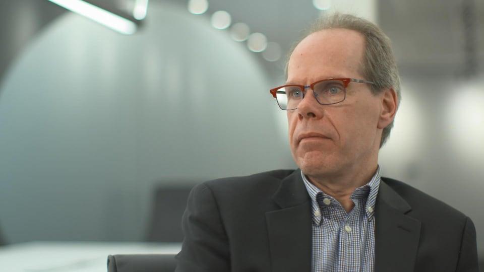L'homme est assis à son bureau, vêtu d'un veston gris et portant des lunettes à la monture rouge.
