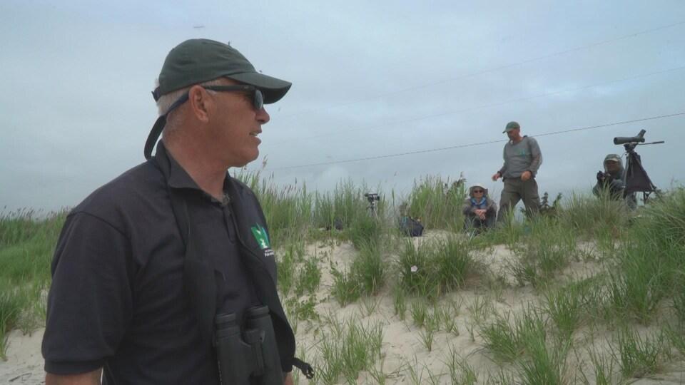 On voit Larry Niles et son équipe sur une dune près de la plage.