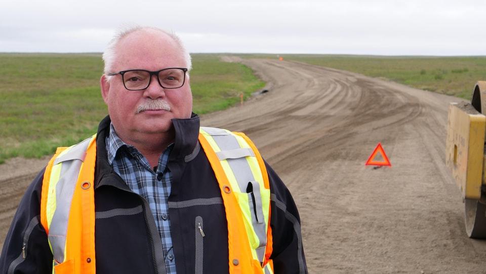 Un homme avec un dossard orange de construction se tient sur une route de gravier en construction.