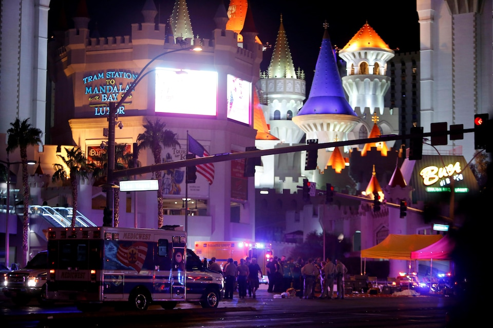 Des policiers et ambulanciers à l'avant-plan et l'hôtel Mandala au fond