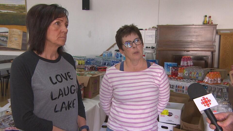 Laura Kowalchuk et Cheryl Desrosiers donne une entrevue placées devant des produits alimentaires collectés.