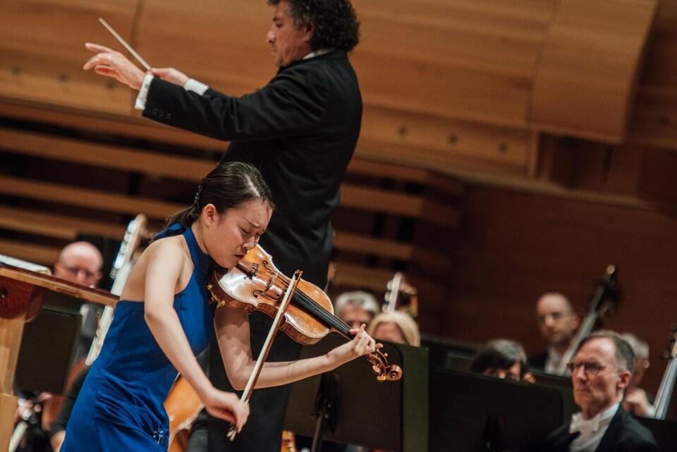 La femme joue du violon devant un orchestre.