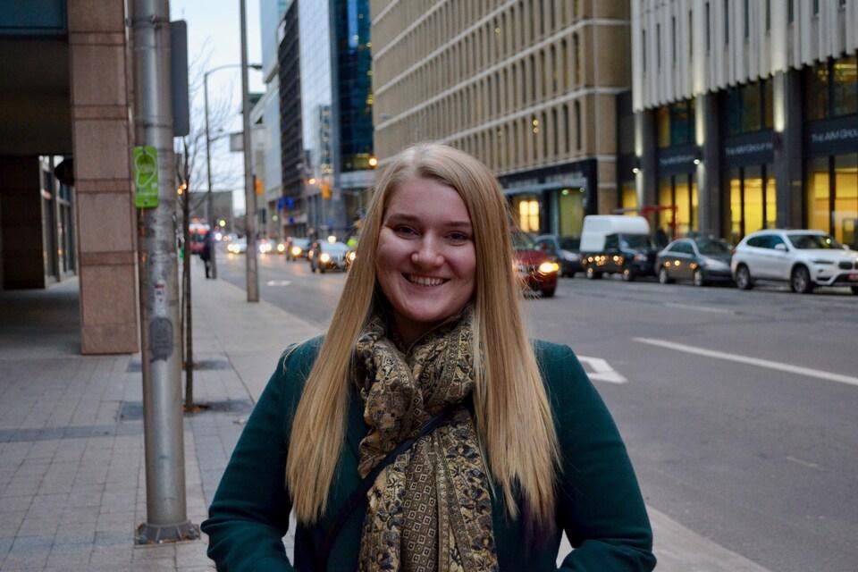 Une jeune femme photographiée devant une avenue par laquelle passent plusieurs voitures