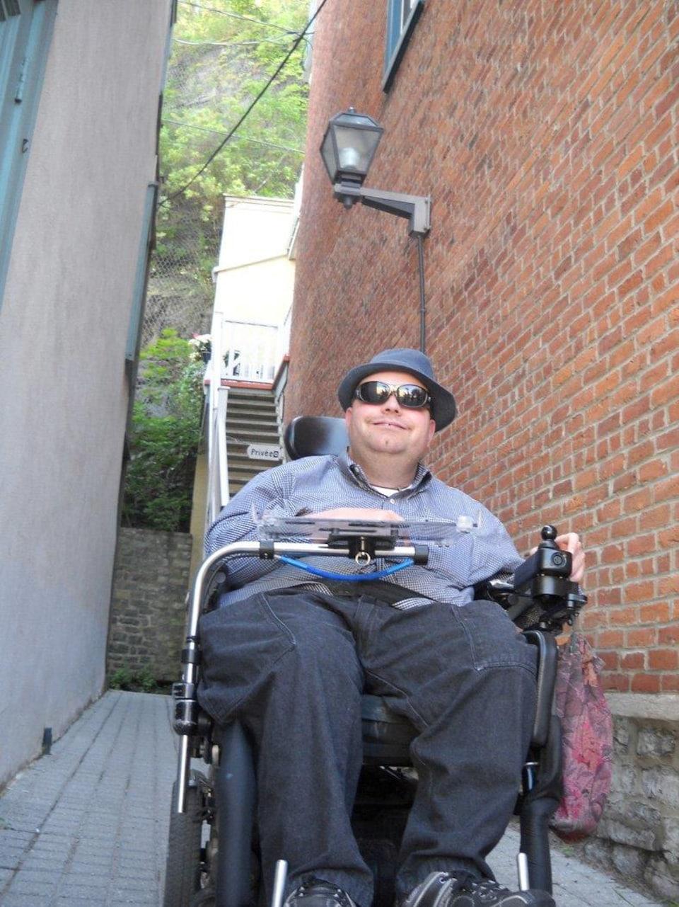 Un homme souriant porte des lunettes-soleil et un chapeau. Il fait face à la caméra. Il est assis dans sa chaise roulante motorisée dans une allée extérieure.