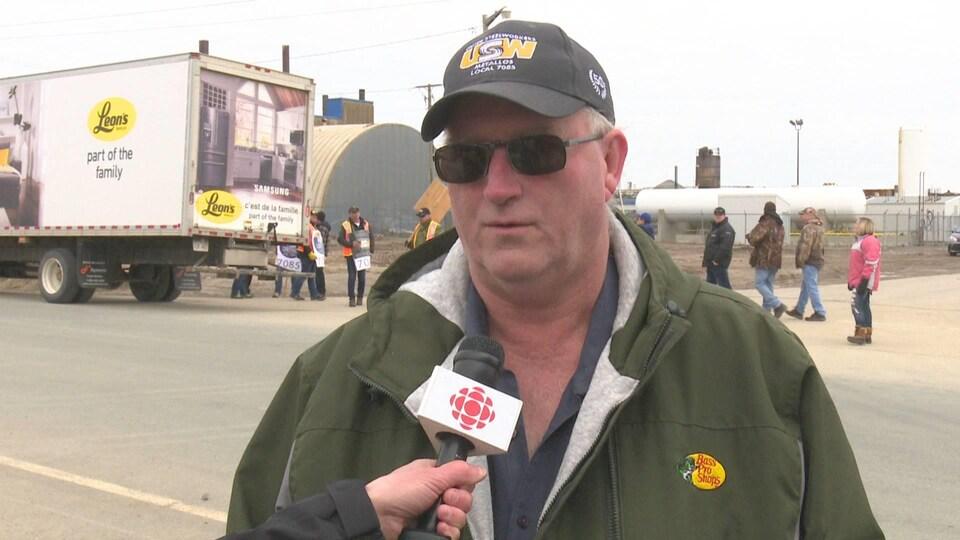 Le représentant syndical parle au journaliste de Radio-Canada devant l'usine et un groupe de grévistes.