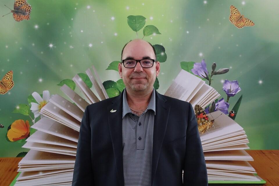 Steeve Paquette, directeur adjoint du CFP de la Baie-James, pose devant une murale à la bibliothèque de l'école secondaire La Taïga.