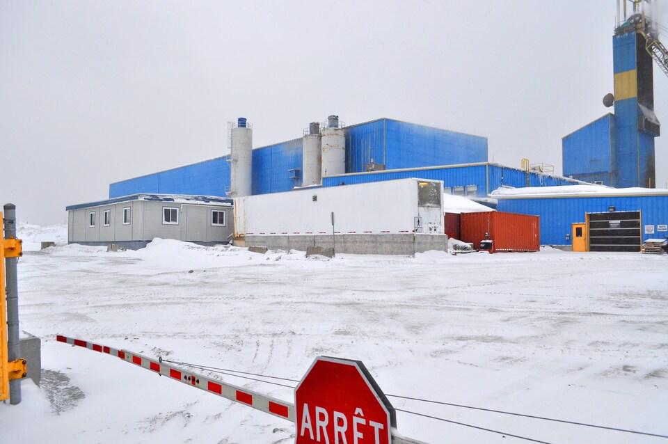 Vue extérieure des bâtiments de la mine Nyrstar Langlois, avec une barrière d'arrêt