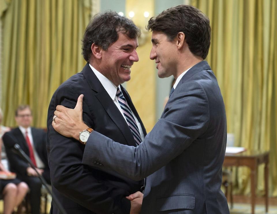 Deux hommes se serrent la main en souriant dans une salle de réception.
