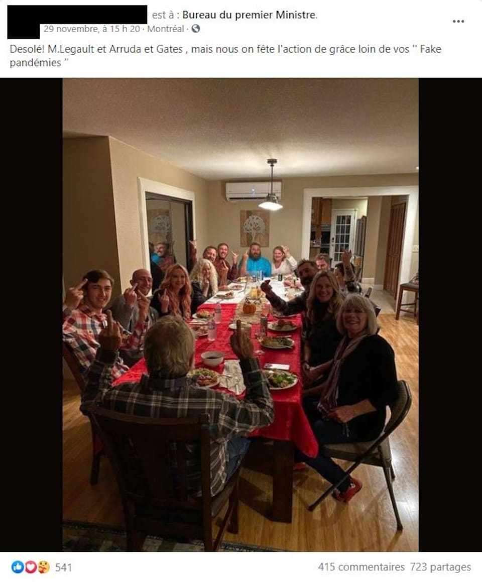 Des personnes rassemblées autour d'une table en mangeant de la dinde font des doigts d'honneur.