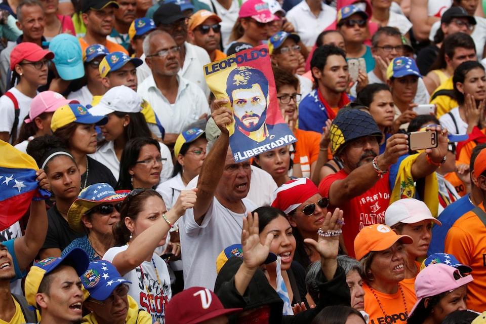 Un homme brandit une affiche avec le visage de Leopoldo Lopez, au milieu d'une foule de manifestants
