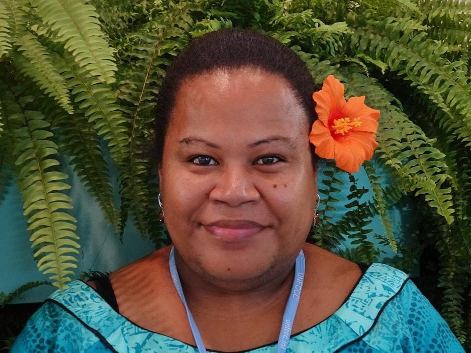 La femme porte une robe turquoise et une fleur orange à la tête.