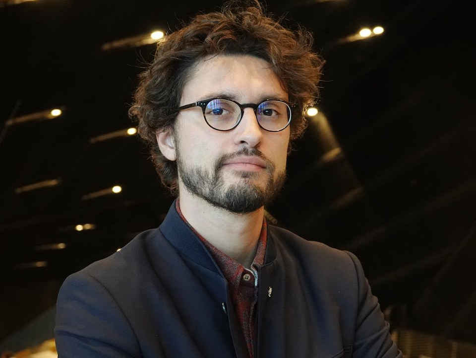 Un homme porte des lunettes et une courte barbe.