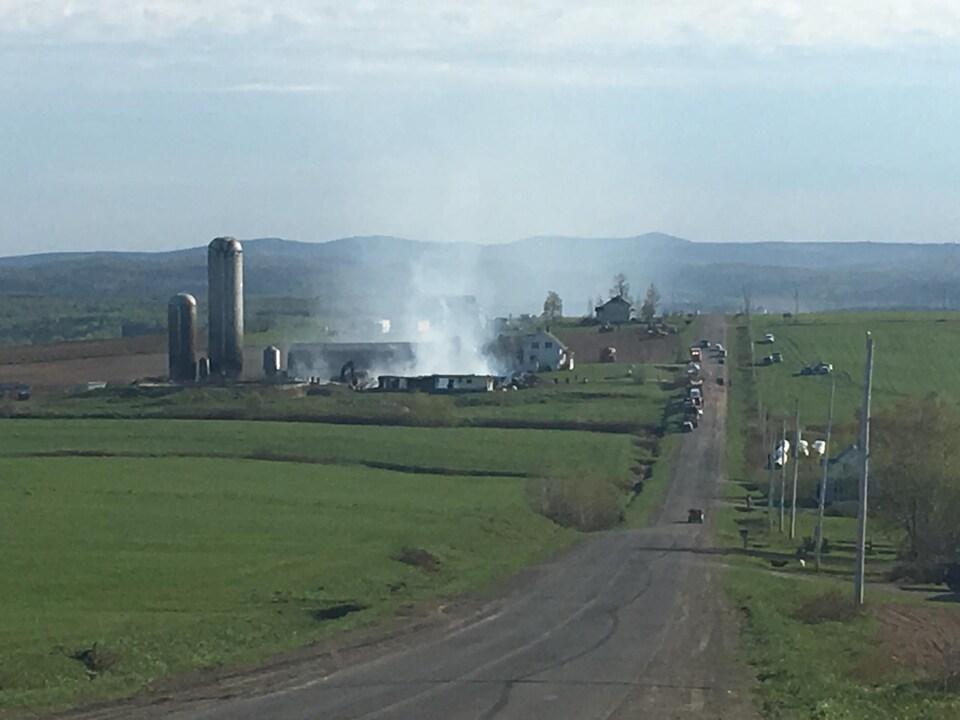 De la fumée se dégage des décombres d'une ferme laitière, après un incendie