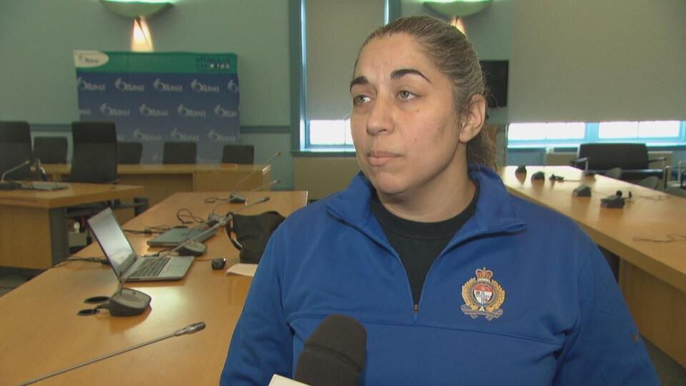 Une femme avec un chandail de la police d'Ottawa en entrevue.
