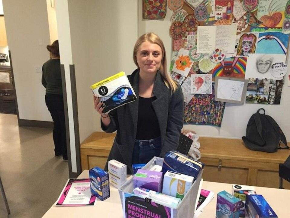 Lindsay Shaw tient une boîte de serviettes hygiéniques