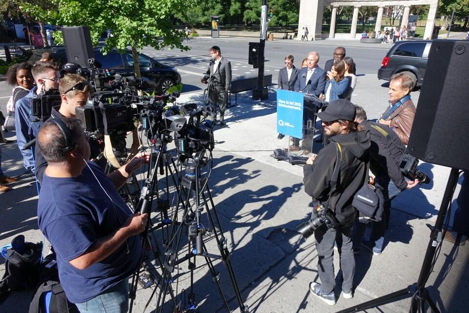 Des caméramans filment le point de presse au coin de McGill College et Sherbrooke Ouest.