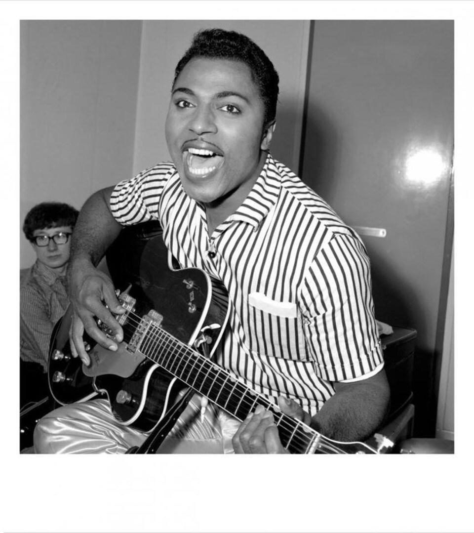 Un homme chante et joue de la guitare électrique.