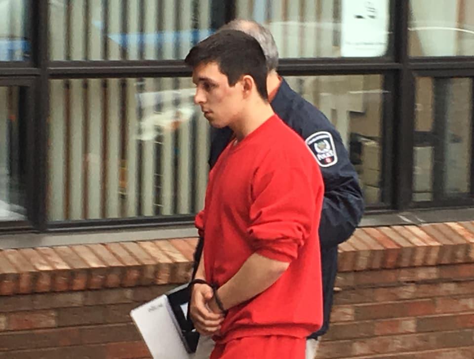 Un prisonnier en combinaison orange est escorté par un policier.