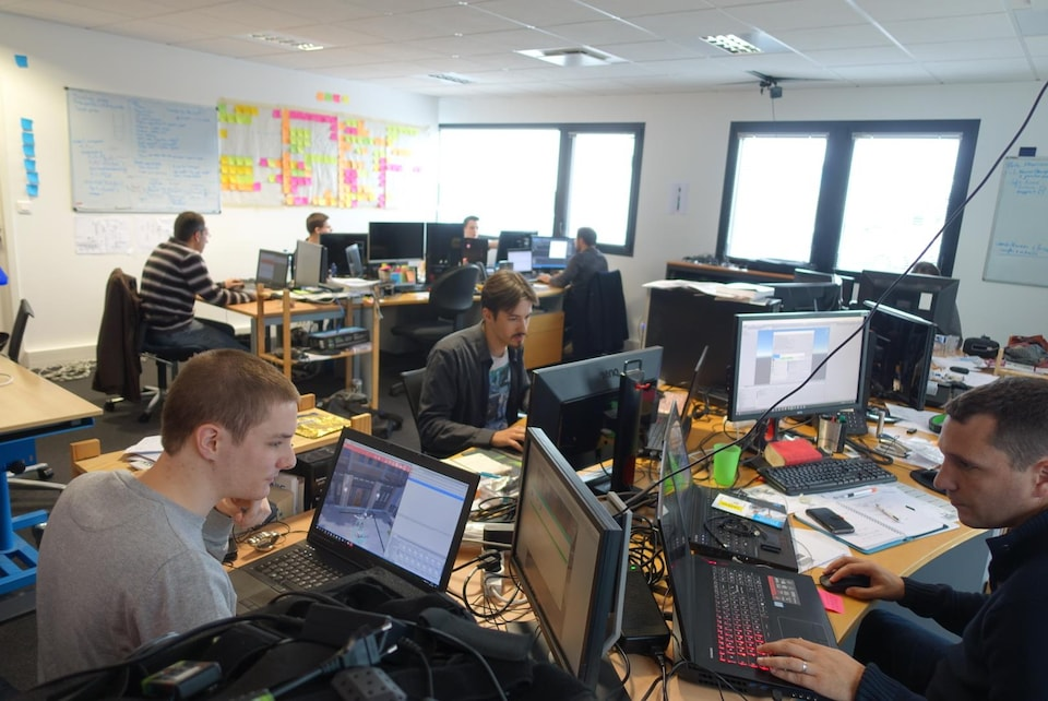 Sept hommes travaillent à leur bureau devant une panoplie d'écrans d'ordinateur.