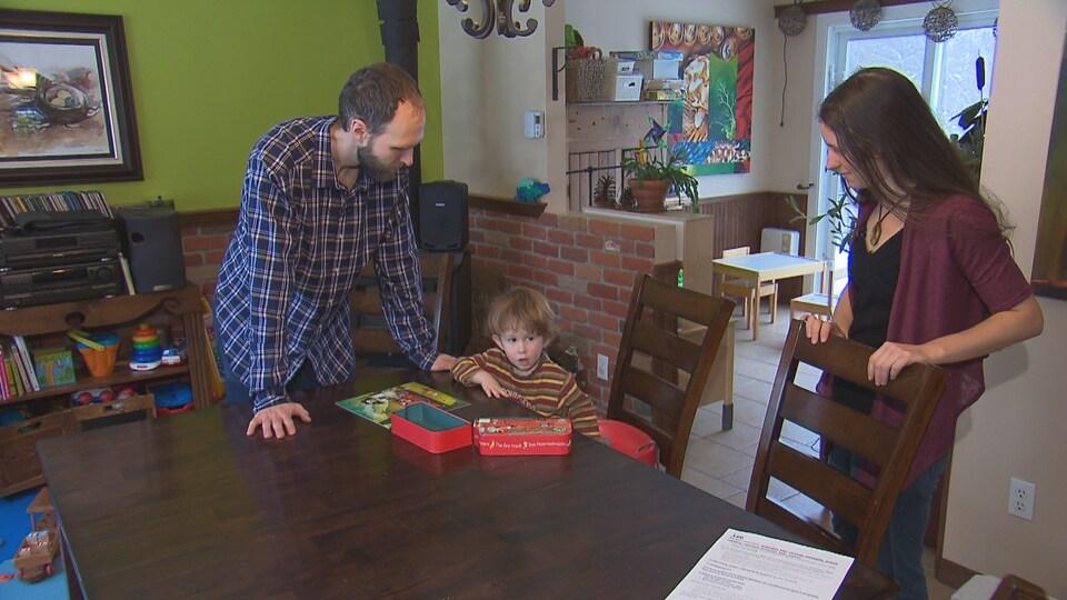 Les deux adultes et le petit garçon sont tous les trois autour d'une table dans une salle à manger.