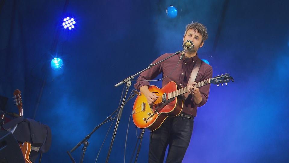 Il chante, avec sa guitare, seul sur scène.
