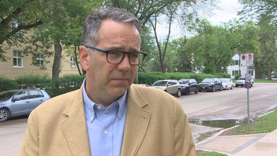 Un homme avec des lunettes présente un air désolé
