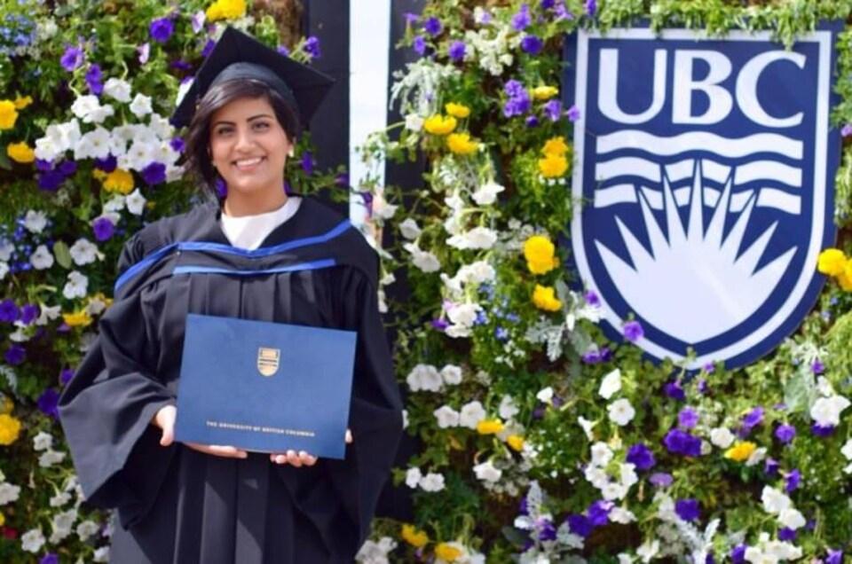 Une jeune diplômé devant des fleurs.